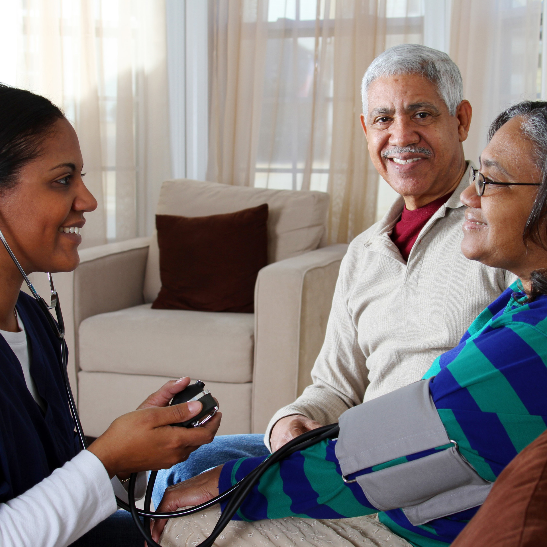 A care worker monitoring residents blood pressure, with partner beside her