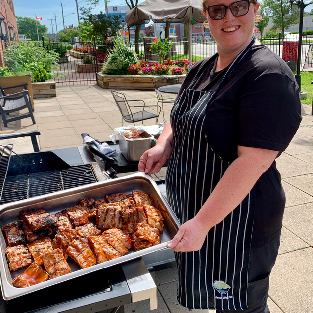 Culinary team member showcasing BBQ grills.