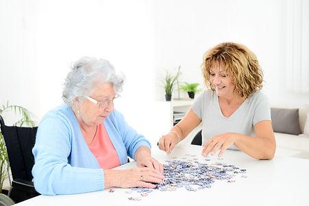 Nurse helping Elderly woman make a puzzle