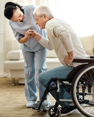 Nurse helping elderly man out of his wheelchair
