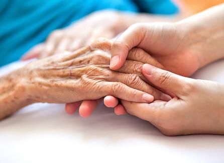 Nurse holding elderly womans hand for comfort