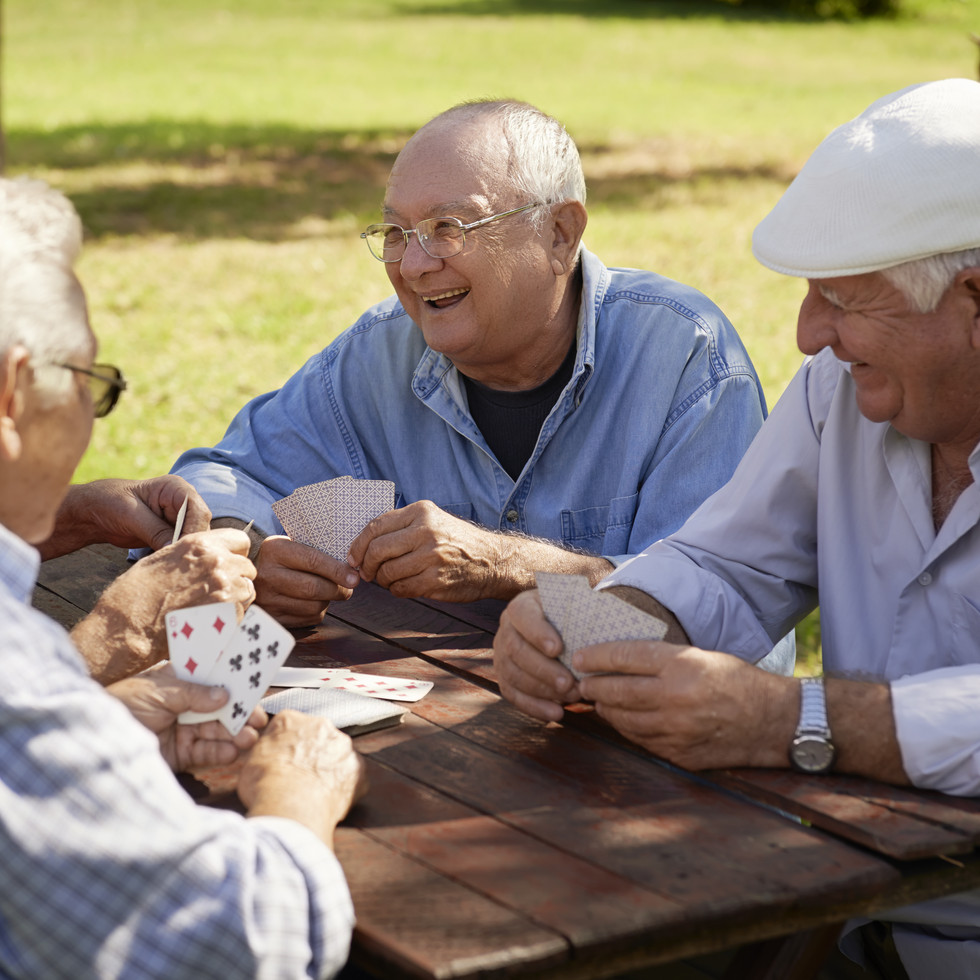 Retirees playing cards on bench outside
