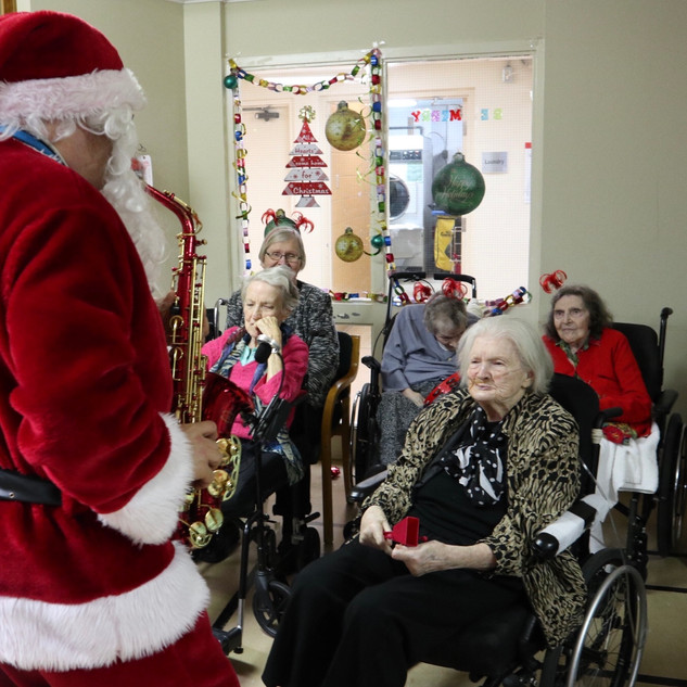 Greenview Christmas - Santa playing saxaphone and residents watching