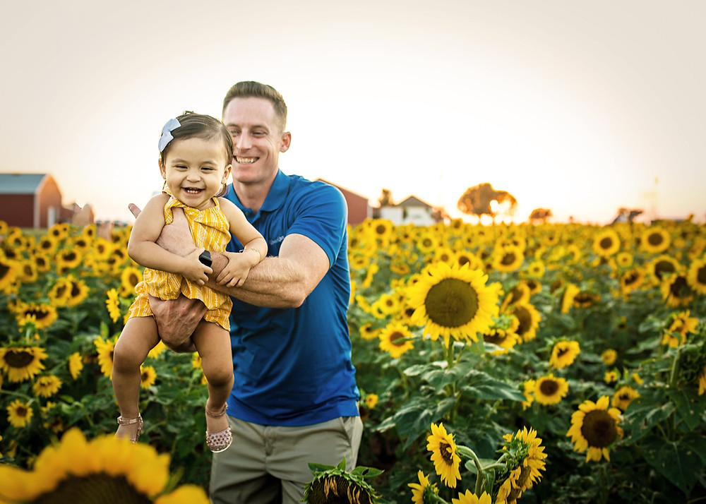 Dad holding baby with sunflowers