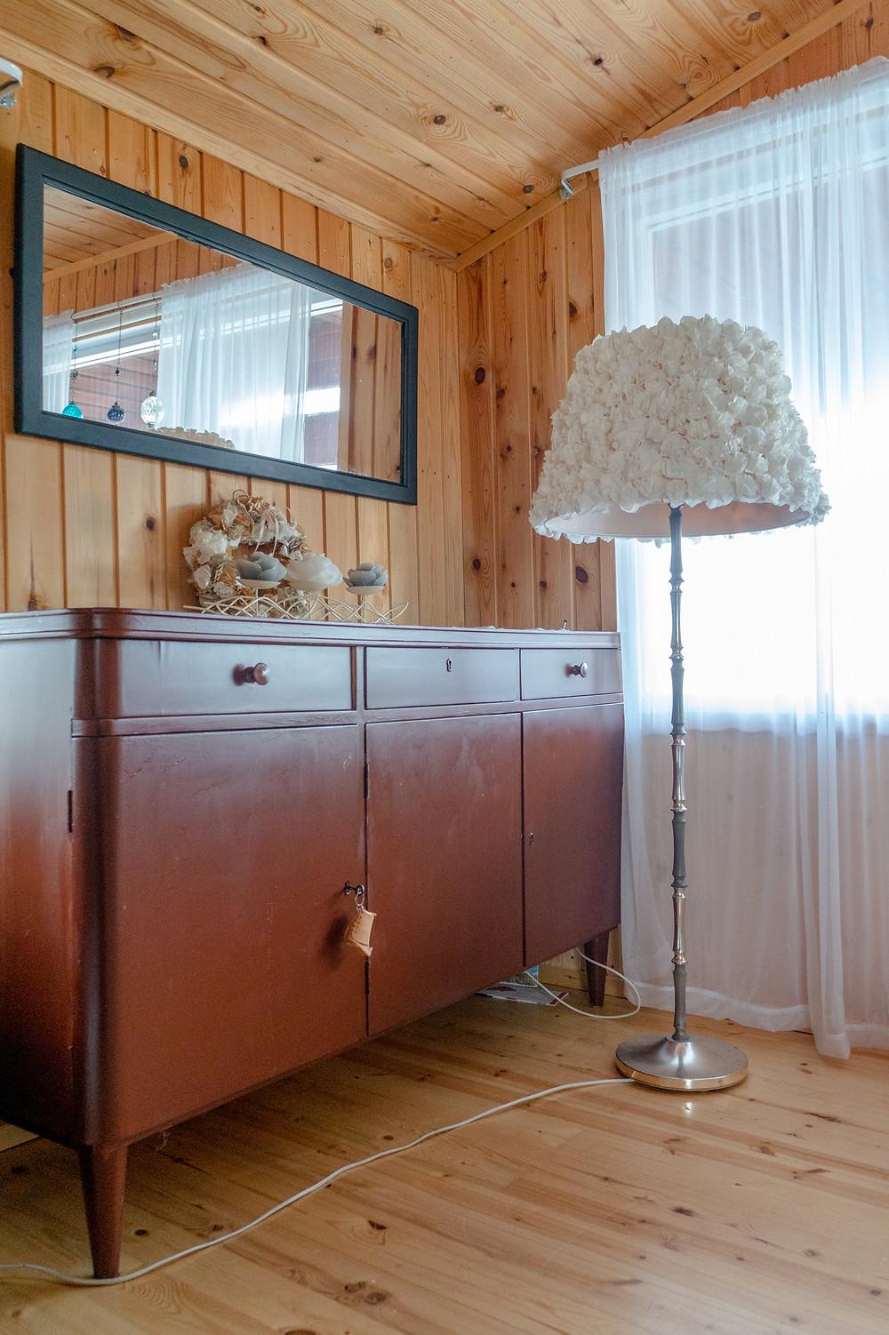 Ikivanha senkki tuli aikoinaan talon mukana. Vanha peili on maalattu sopiakseen paremmin sisustukseen. Kynttiläkoriste ja jalkalamppu kirpputorilta (varjostimen ruusut tehty itse suodatinpusseista; samoja ruusuja on kranssissa).