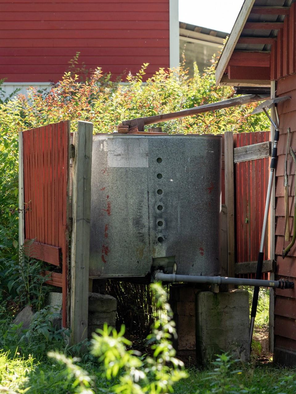 Sadeveden kerääminen vesikouruist. Vesi johdetaan putkesta saunaan