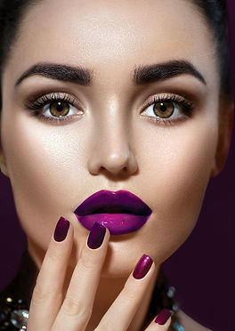 A beautiful woman with sculpted eyebrows, smooth skin, long lashes, plump lips, and painted fingernails.