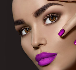 A beautiful woman with sculpted eyebrows, smooth skin, long lashes, and full purple lips.