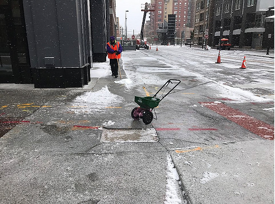 CSG team member salting and brushing a sidewalk in downtown Denver, CO