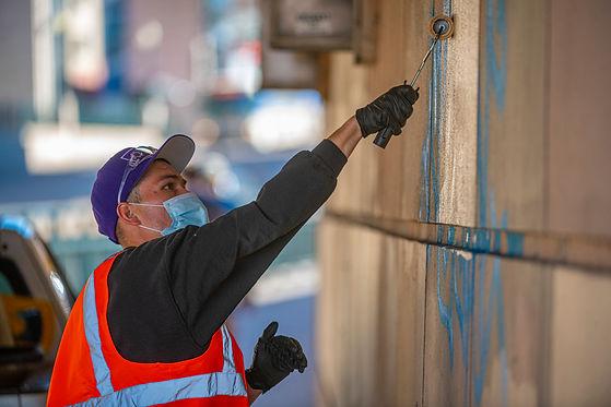 CSG team members carefully remove graffi