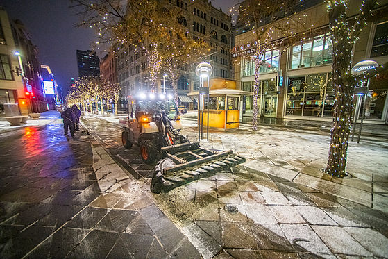 CSG staff using a plow and brooms to clear snow on 16th street mall