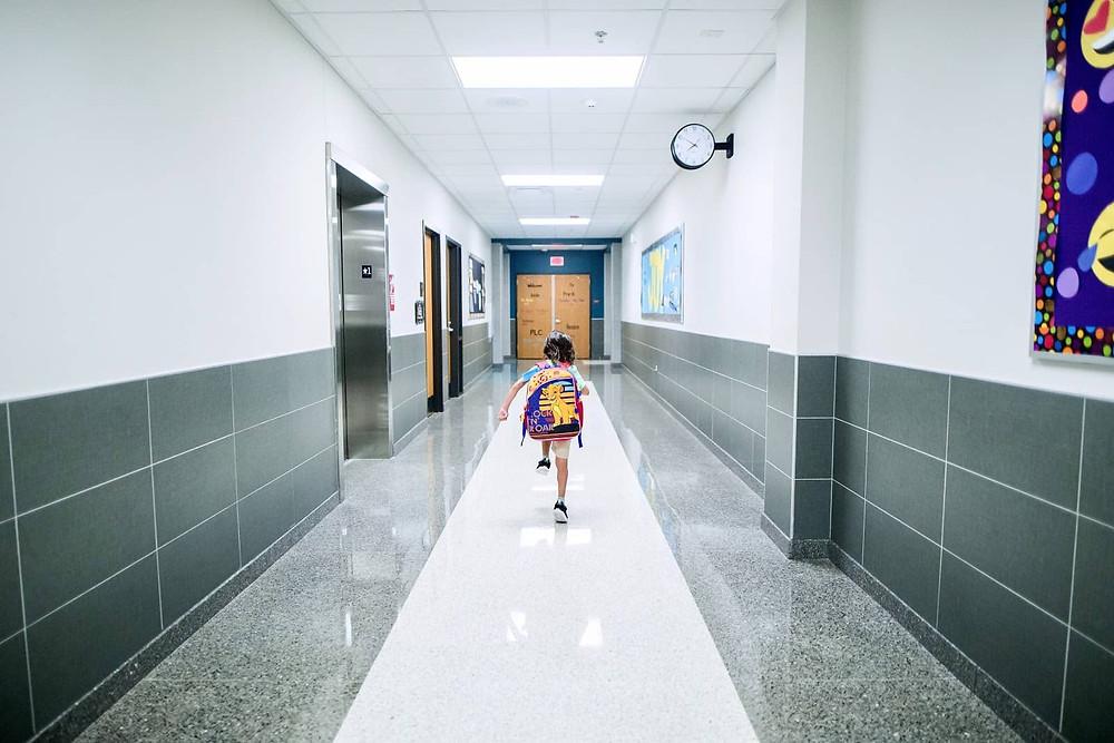 child running in a school hallway