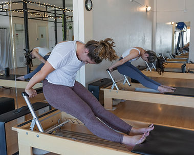 Reformer exercises executed by 2 women at ABQ Somos Pilates