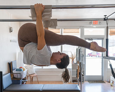 Woman demonstrates pose suspended from the Pilates Cadallic equipment