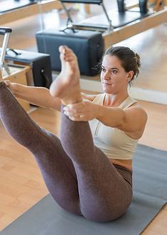 Woman engaged in Open Leg Rocker exercise