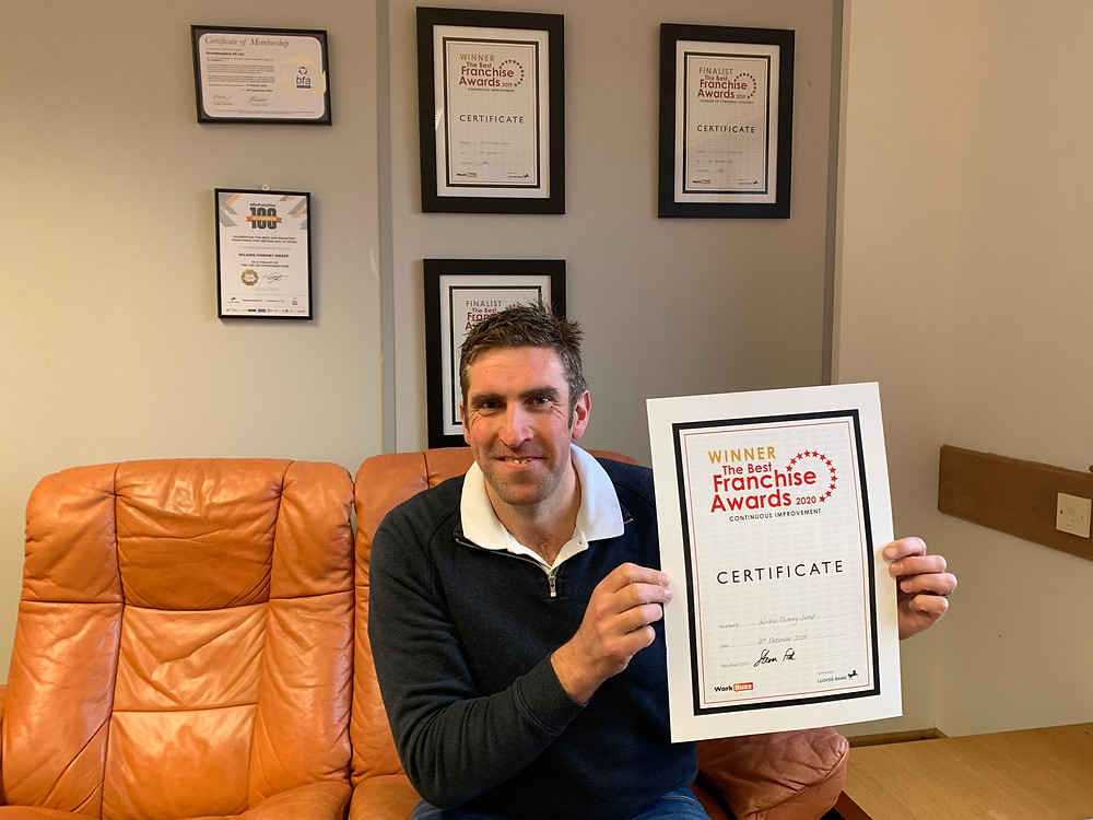 A man, sitting on a sofa, holding up a certificate