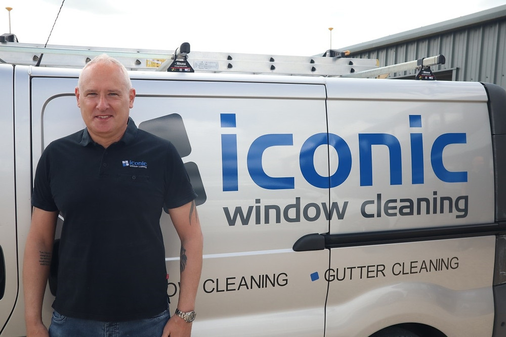 A man is standing in front of a silver van. Along the side of the van we can read the writing Iconic Window Cleaning. The man is smiling.