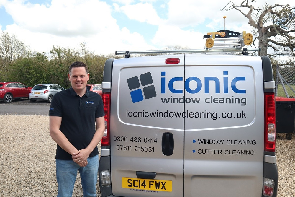 A man is standing beside the back of a van. He is wearing a black polo shirt and blue jeans. The back of the van has the name Iconic Window Cleaning written on it with a logo.