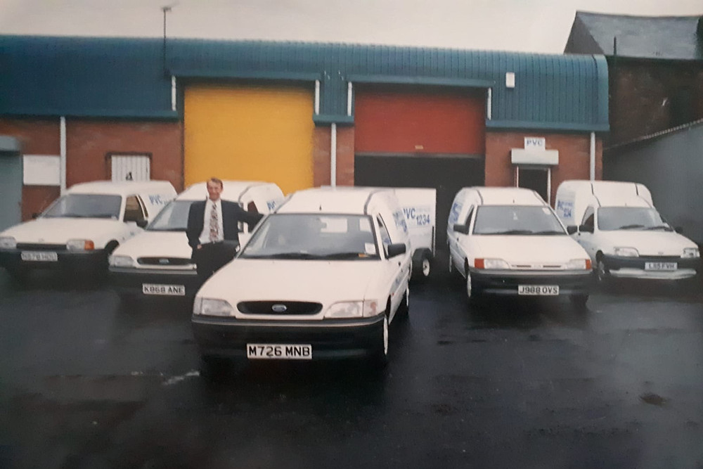 A man in front of five white vans