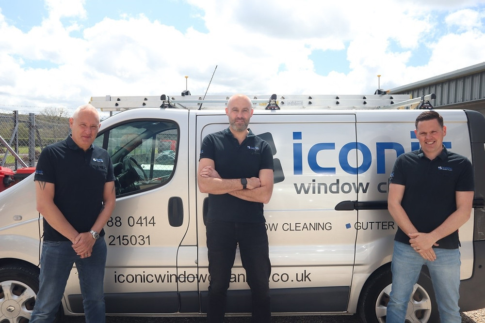 Three men, standing in front of a white van with blue and grey writing on it. There are clouds in the sky. The van has ladders on the roof.