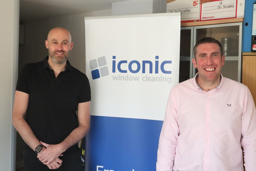 Two men standing either side of a pop up banner that says Iconic Window Cleaning on it. They are both smiling.