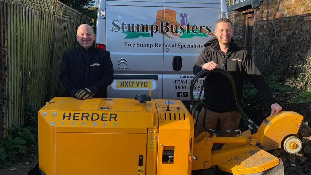 Two men in black jackets stand between a white van with the logo 'Stumpbusters' on it and a yellow stumpgrinder with the name Herder on it. They are smiling.
