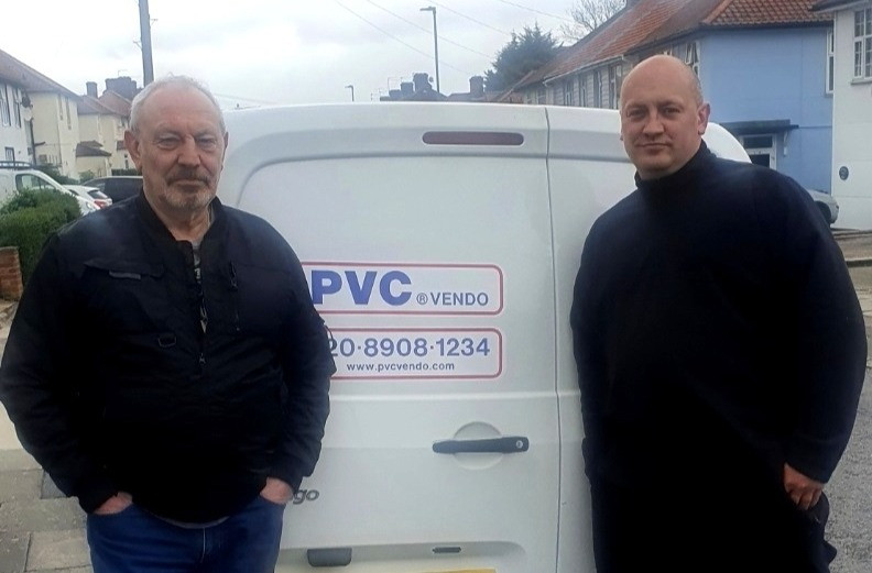 Two men standing in front of a white van.