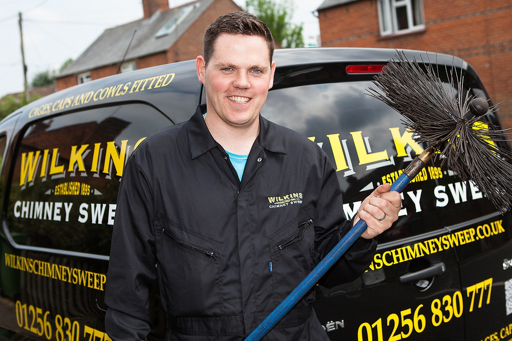 A young man in black work overalls holding a chimney sweeping brush with a blue handle, standing in front of a black van with yellow and black sign writing on it.