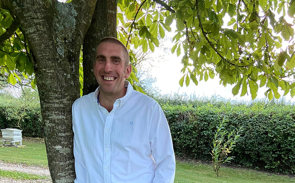 A man wearing blue jeans and a white shirt is leaning against a tree in a garden. He is smiling.
