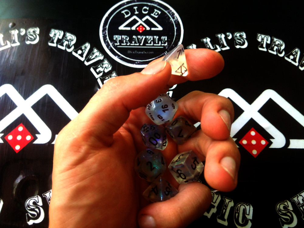 Hand holding many dice over Dice Travel Logo