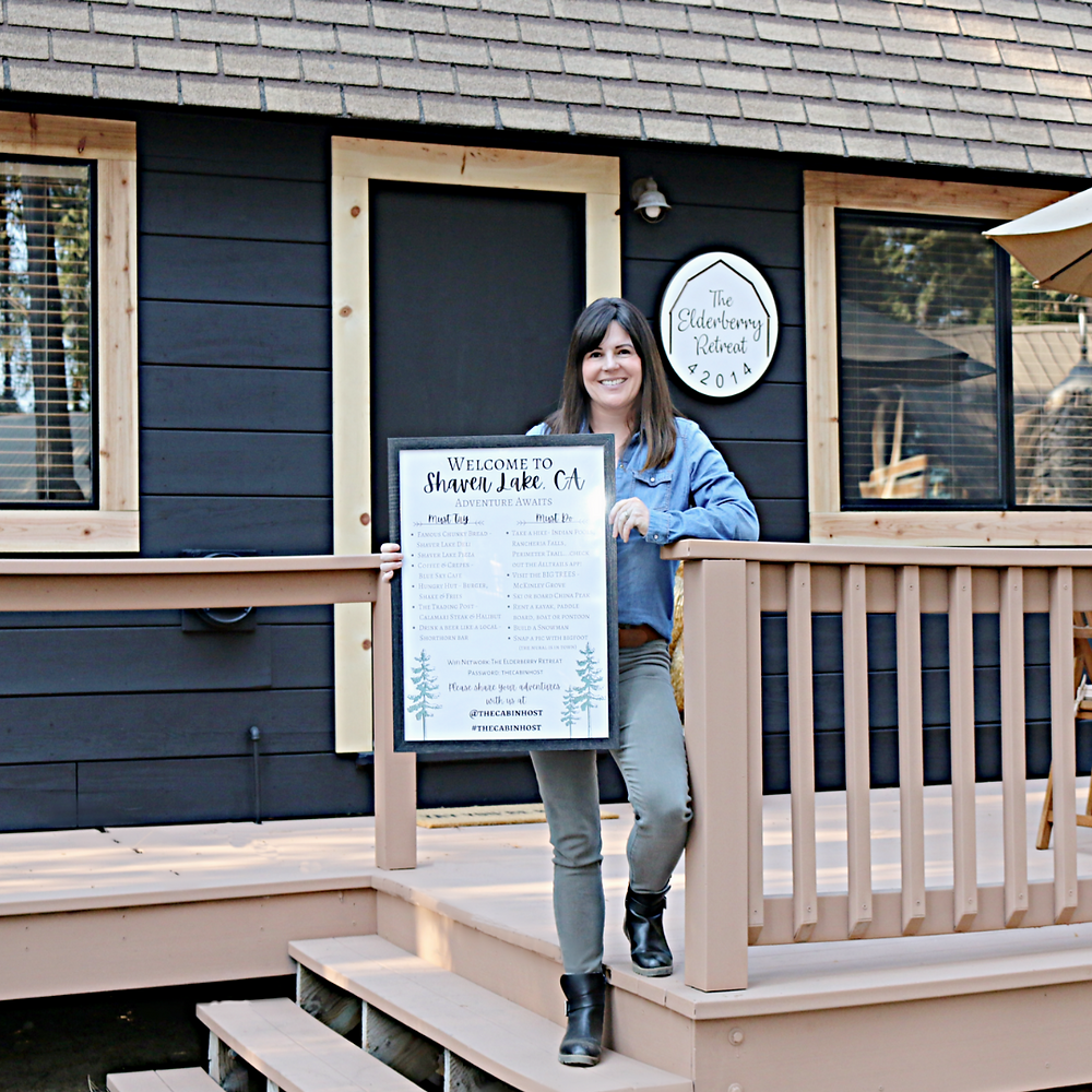 Host holding a welcome poster at a cabin