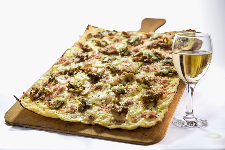 The flammekueche is a traditional dish from the east part ofFrance consisting of a thin bread dough covered with thick cream and cheese, and topped with smoked bacon, onions an then shortly baked into a hot oven