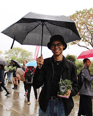 Cornell student enjoying a free plantin the rain