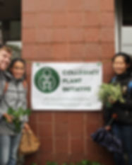 Cornell students in front of a Collegiate Plant Initiative sign at a Plant Drop