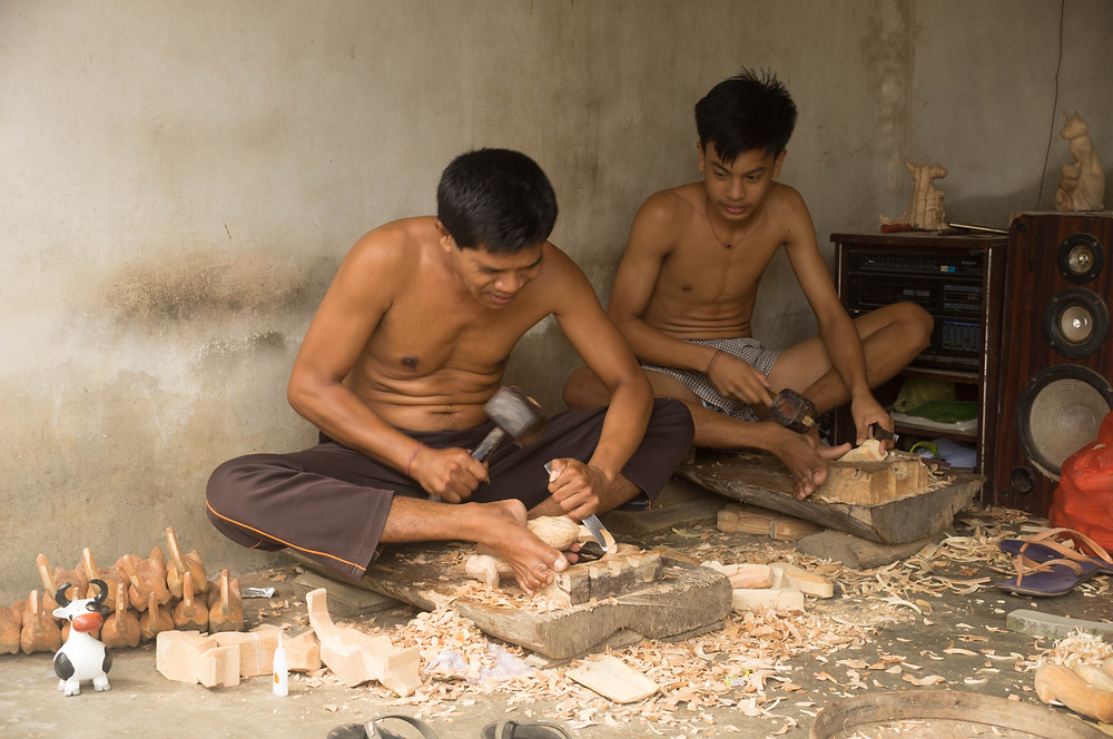 A father and his son work together in woodcarving. Skills are often taught through families.