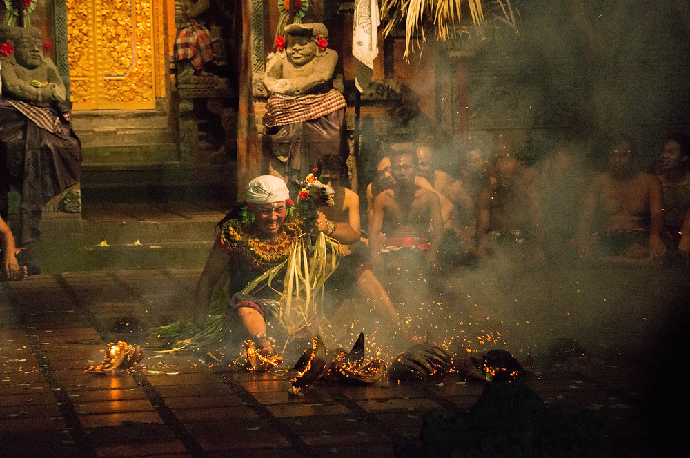 Jumping repeatedly into the embers of a fire, a man dances barefoot atop the pile of coconut fibers, performing the Balinese Fire Dance. The Sanghyang song chanted by the choir of men may lead him into the flames as he connects to their gods or ancestors, unable to feel pain in the state of trance.