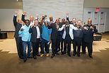 Exonerees smiling and raising hands of freedom