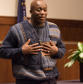 Darryl standing with hands on chest as he gives a presentation