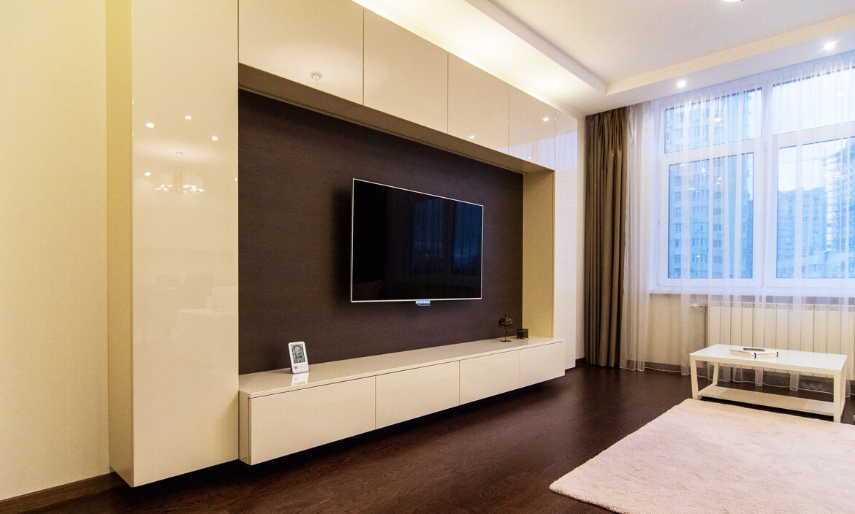 Стенка в гостиную с зоной для телевизора с бежевыми глянцевыми фасадами