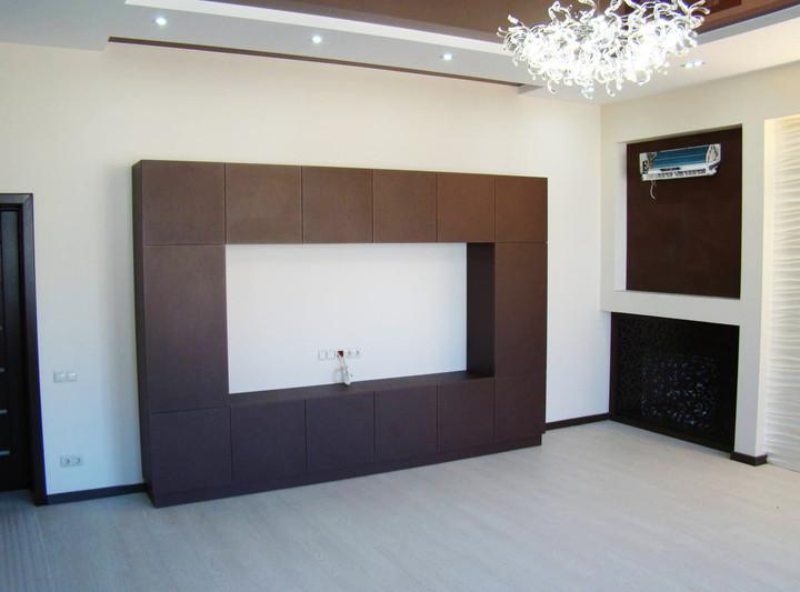 Стенка в гостиную с зоной для телевизора с фасадами облицованными искусственной кожей
