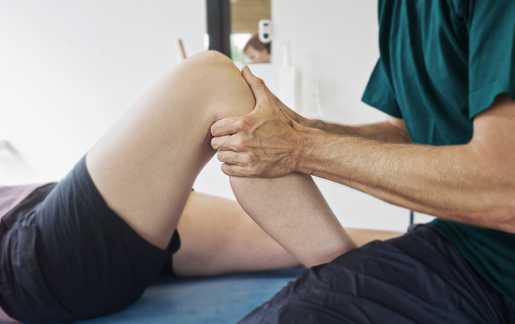 Physiotherpist working on a knee-bend