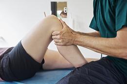 Osteopath holding patient's bent knee