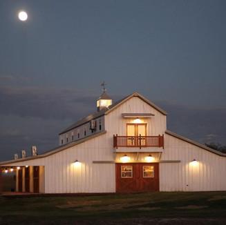 big white barn at dusk