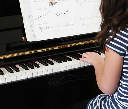 Young girl playing beginner piano
