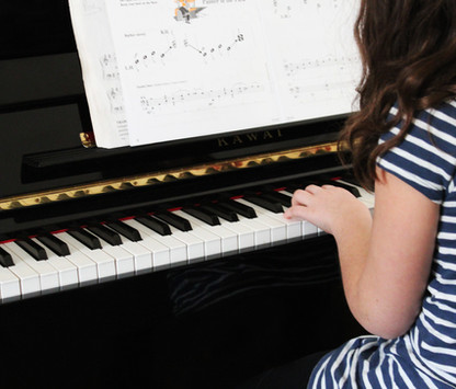 Young girl playing beginner piano