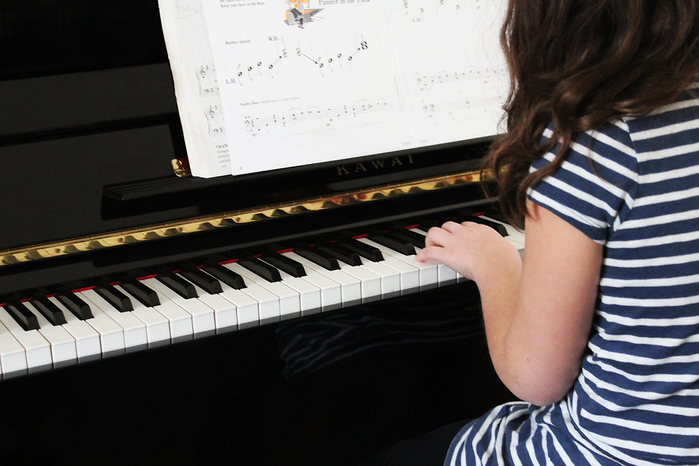 Girl Learning beginner piano music at piano