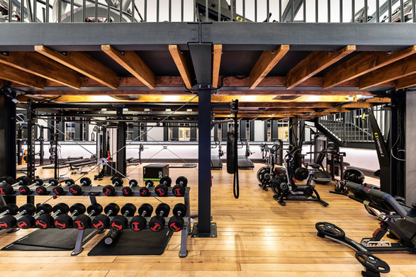 Photo of Luxe Fitness Boutique Gym with architect designed industrial steel mezzanine in barrel vaulted first floor of listed building.
