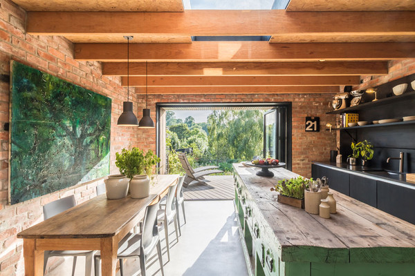 Kitchen of Miner's Cottages. Rustic industrial styling with brick interiors and black kitchen with feature rustic kitchen island.
