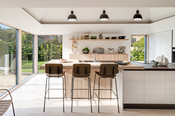 Interior photo of kitchen pavilion of Design Storeys Arts & Crafts House. Vaulted ceiling with lighting slot and contemporary. Pendini kitchen and open shelving.