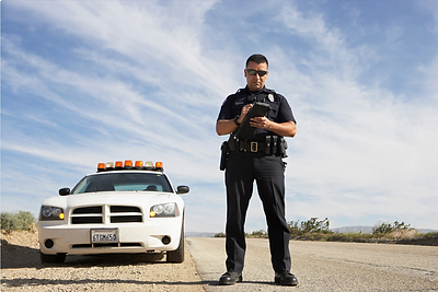Officer In front of car writing speeding ticket